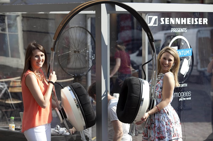EDITORIAL USE ONLY (Left to right) Olivia Allen and Rachael Head pose with a oversized pair of headphones at a Giant Sound Bubble in London's Covent Garden, which is part of Sennheiser's What's Your MOMENTUM campaign in conjunction with Mogees, a device that turns everyday objects into musical instruments. PRESS ASSOCIATION Photo. Picture date. Thursday June 19, 2014. Photo credit should read: David Parry/PA