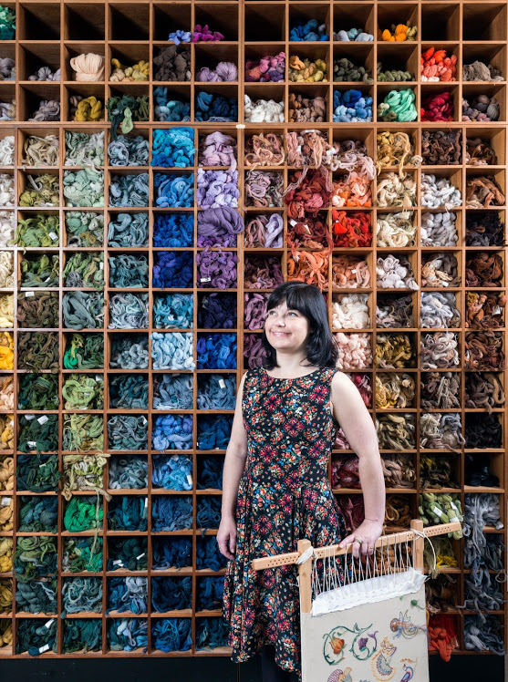 Kate Barlow, In front of the'Wall of Wool', Royal School of Needlework. Kate is a current Future Tutors student at the Royal School of Needlework. Founded in 1872 and based in Hampton Court Palace, the Royal School of Needlework is the international centre of excellence for the art of hand embroidery. © Historic England/Chris Redgrave